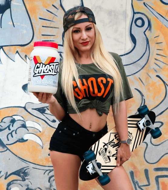 sporty young woman holding a tub of ghost nutrition vegan protein