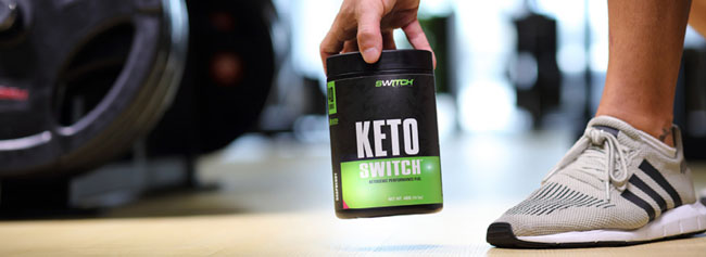 man picking up a tub of keto switch