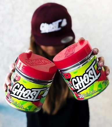 woman holding 2 tubs of ghost BCAAs