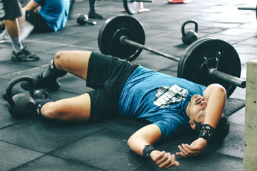 Man resting next to barbell on the floor